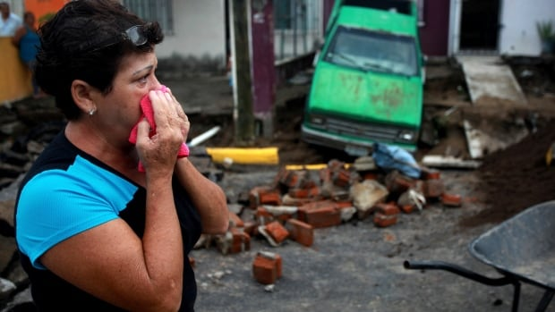 Maria del Carmen Gonzalez watches after part of a street and her home collapsed due to heavy rains in the Gulf port city of Veracruz, Mexico, Tuesday Sept. 2, 2014.