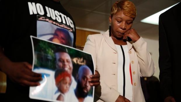 Lesley McSpadden, the mother of 18-year-old Michael Brown, wipes away tears as Brown's father, Michael Brown Sr., holds up a family picture of himself, his son, top left, and a young child during an Aug. 11 news conference in Jennings, Mo. Two news organizations seek the release of any possible juvenile records for the unarmed 18-year-old who was shot by a police officer last month.