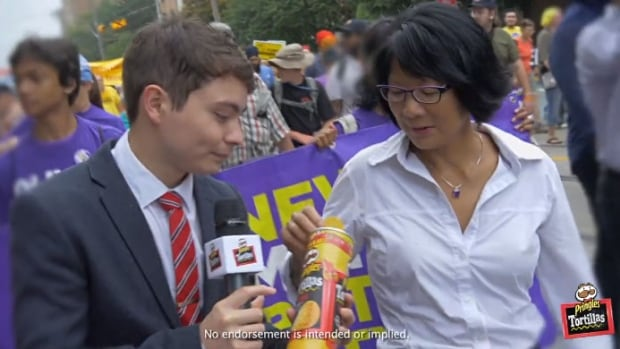 Olivia Chow, marching in the Labour Day parade, stopped to appear in a Pringles commericial.