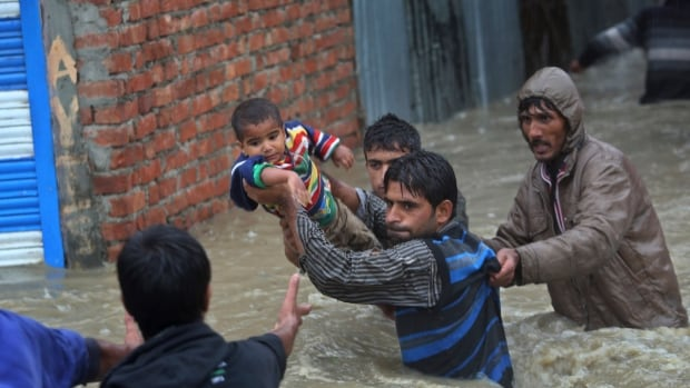 Kashmiri men carry a boy to safety after their neighborhood was flooded in Srinagar, India, on Thursday.