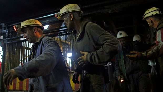 Injured coal miners emerge from the mine on Friday after 34 miners were trapped half a kilometre underground. Twenty-nine were freed but the rescue mission was halted with five miners still missing.