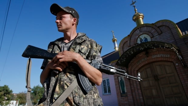 A pro-Russian separatist stands guard near an orthodox church in the eastern Ukrainian town of Ilovaysk. Ukraine and pro-Russian rebels agreed a ceasefire on Friday, the first step towards ending fighting in eastern Ukraine that has caused the worst standoff between Moscow and the West since the Cold War ended.