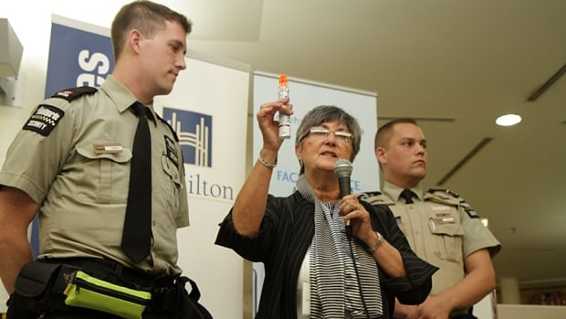 Marilyn Allen of Anaphylaxis Canada demonstrates how the auto injectors work with Jackson Square security guards Michael Thibodeau and Spencer Porter at the launch of the pilot program in September 2014. The city is expanding the project to 50 restaurants.