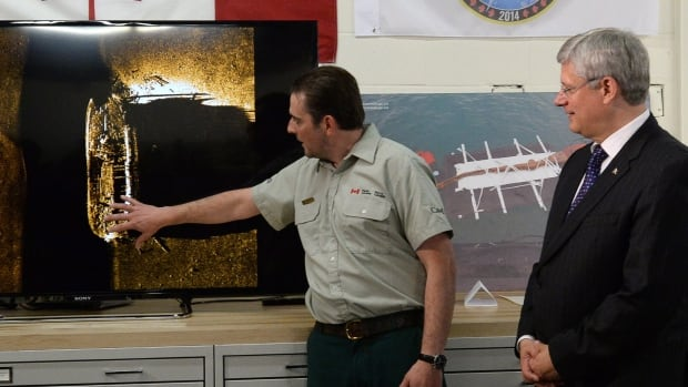Prime Minister Stephen Harper listens to details from Parks Canada's Ryan Harris about the discovery of one of the ships from Sir John Franklin's Arctic expedition, which was lost in 1846.