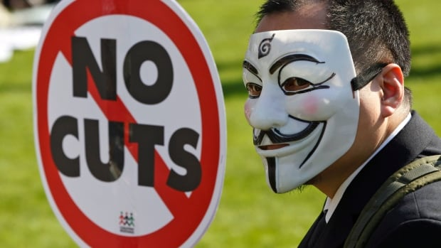 A masked protester holds a placard and wears a Guy Fawkes mask, something that's become a symbol of the global protest movement against income inequality.  The Broadbent Institute says it's also a worsening problem in Canada.