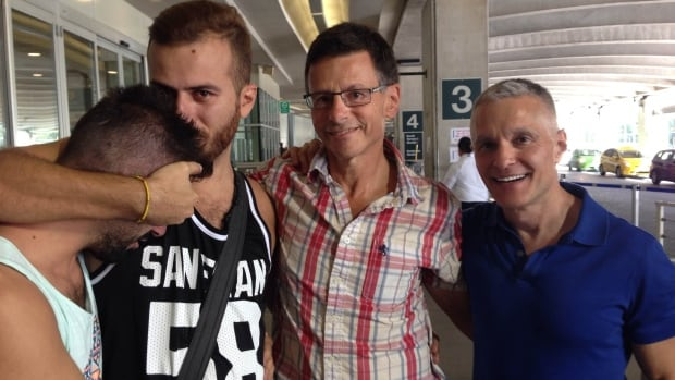 Aamer, whose face is obscured because he's not out to his family, and his partner Danny Ramadan arrive at Vancouver International Airport, thanks to sponsors David Salter and Ron Rosell, at right.