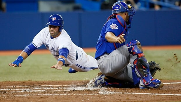 Kevin Pillar, left, of the Toronto Blue Jays slides in safely ahead of the throw to catcher Welington Castillo in 2014. The Blue Jays are looking into whether they can install natural grass in the Rogers Centre, which now has artificial turf.