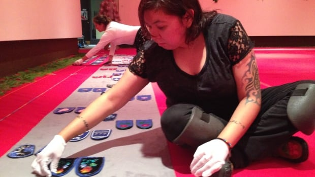 Kara Louttit begins the process of laying out more than 1700 moccasin vamps (tops) for the Walking With Our Sisters installation at the Thunder Bay Art Gallery. The exhibit opens Friday.