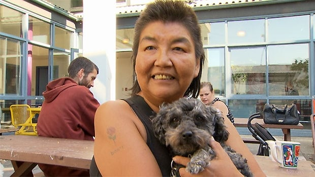 Marilyn sits outside the free pet clinic Sunday waiting to have her dog Max's eyes checked.