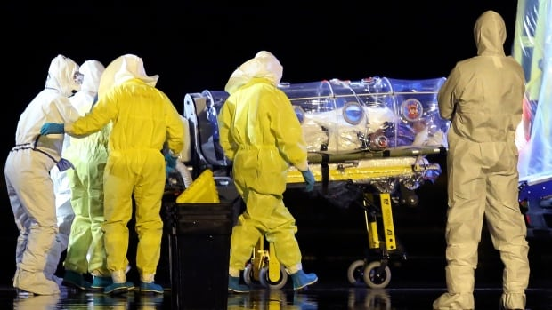 Aid workers and doctors transfer Manuel Garcia Viejo, a Spanish priest who was diagnosed with the Ebola virus while working in Sierra Leone, from a military plane to an ambulance, near Madrid on Monday.