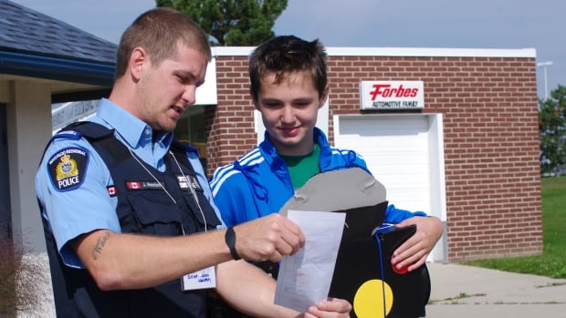 Special Constable John Heaton and Matthew Colombo work together to find traffic signs at the Children's Safety Village in Cambridge.