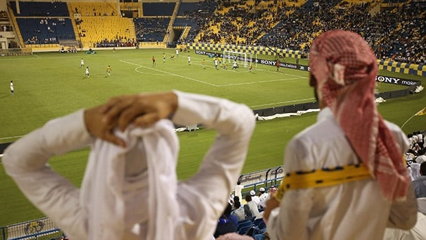 Fans watch a football match in Doha, Qatar. The 2022 World Cup tournament has been dogged by charges of corruption in the bid process, and over the country's labour practices.