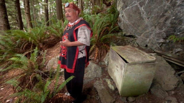 Aboriginal tourism operator Tom Sewid stands near a First Nations burial box on a remote Island in British Columbia's Broughton Archipelago in an undated handout photo. Sewid's actions, giving travellers full access to ancient burial boxes, including revealing the skeletal remains, have been condemned by his fellow First Nations.