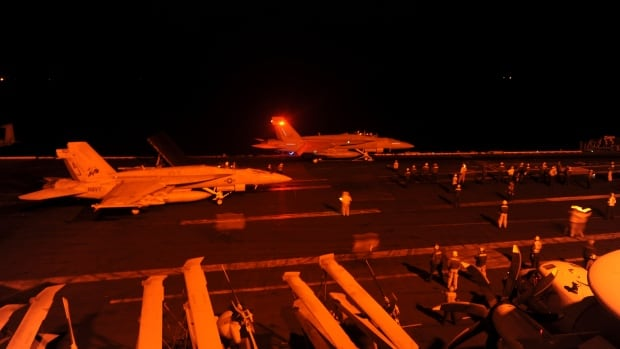 Two Super Hornets prepare to launch from the flight deck of the aircraft carrier USS George H.W. Bush on Tuesday. On Thursday, U.S.-led airstrikes targeted Syrian oil installations.