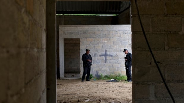 Mexico state police stand inside a warehouse in July where a black cross covers a wall near blood stains on the ground after a shootout between Mexican soldiers and alleged criminals on the outskirts of the village of San Pedro Limon, in Mexico state, Mexico.  Mexico's Defence Department says an army officer and seven soldiers have been detained in connection with the killing of 22 people in the rural town in southern Mexico.