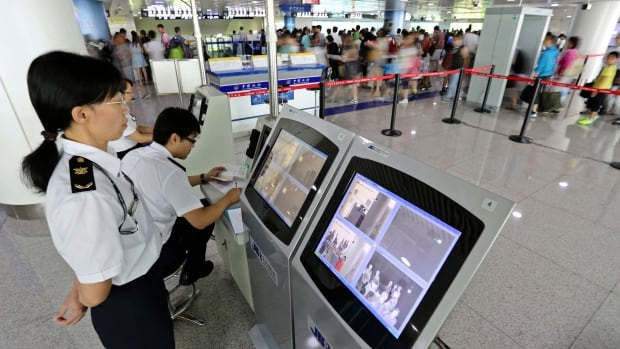 Passengers arriving at Qingdao airport in China are screened for their temperature as part of escalating efforts to contain the Ebola outbreak in West Africa.