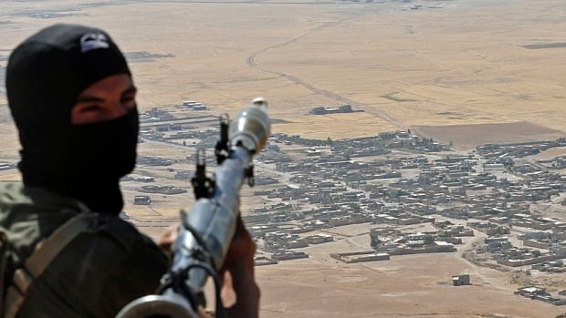 A Kurdish Peshmerga fighter holds a a rocket-propelled grenade launcher as he takes up position in an area overlooking Baretle village (near Mosul in north-central Iraq), which is controlled by ISIS.