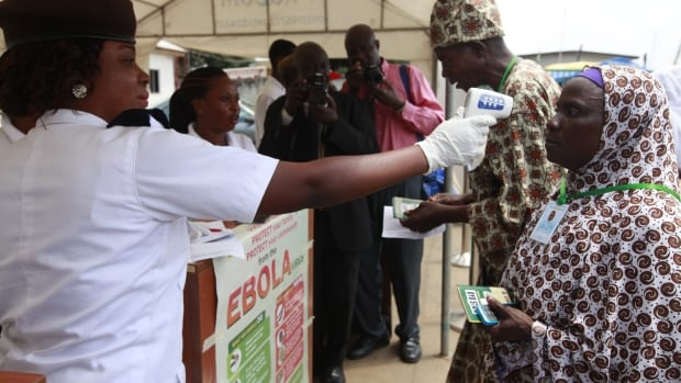 A Nigerian port health official uses a thermometer to screen Muslim pilgrims for Ebola at the Hajj camp before boarding a plane for Saudi Arabia at the Murtala Muhammed International Airport in Lagos. Thousands of people were screened per day per point of entry.