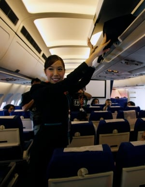 carry-on baggage stewardess flight attendant airplane overhead