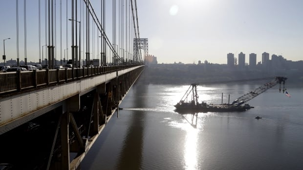 A large crane named the Left Coast Lifter heads underneath the George Washington Bridge in Fort Lee, N.J. The IMF boosted its forecast for U.S. growth to 2.8 per cent this year.