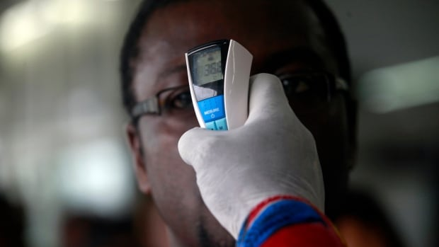 A health worker takes a passenger's temperature with an infrared digital laser thermometer at the Felix Houphouet Boigny international airport in Abidjan. Closing the borders to Ebola-affected countries is worsening the financial toll of the disease, the World Bank says.