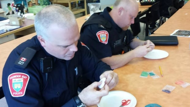 "Two Thunder Bay police officers take part in one of the community 'bead-ins"" organized as part of the Walking With Our Sisters outreach in the city."