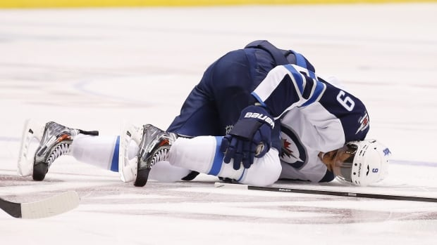 Winnipeg Jets' Evander Kane grabs for his injured right knee as he stays on the ice during the first period of the Jets season-opener against the Arizona Coyotes.