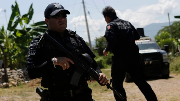 Federal police officers have taken over an investigation into a mass grave near the city of Iguala after accusations of collusion between local police and drug cartels.