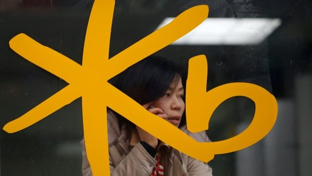 A customer talks on the phone behind the logo of KB Kookmin Financial Group at a branch of KB Kookmin Bank. The theft of personal information from more than 100 million South Korean credit cards and accounts, reportedly including those of President Park Geun-hye and UN chief Ban Ki-moon, has ignited a storm of anger and litigation against credit firms.