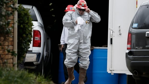 A Protect Environmental Services worker wears a hazard suite in a staging area at the  Dallas apartment of a Texas nurse who tested positive for Ebola. Canadian officials have cited the country's 2003 experience with SARS and lessons learned from that outbreak as evidence that Canadians are better prepared for an infectious disease outbreak than their American counterparts.