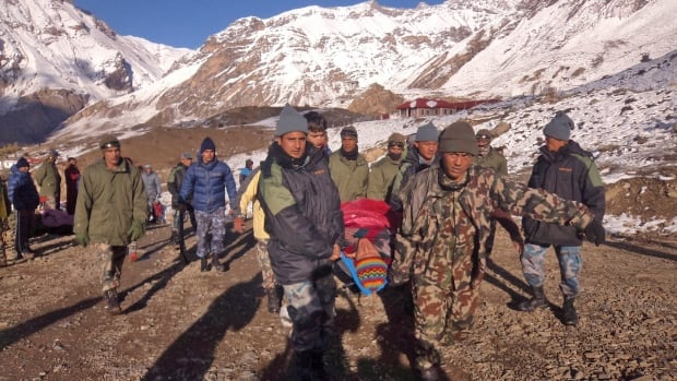 In this photo provided by the Nepalese army, soldiers carry an avalanche victim before he is airlifted in the Thorong La pass area of Nepal. An avalanche and blizzard in Nepal's mountainous north have killed more than a dozen people, including eight foreign trekkers, officials said Wednesday.
