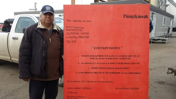 A protester stands with an oversized eviction notice for Manitoba Hydro.