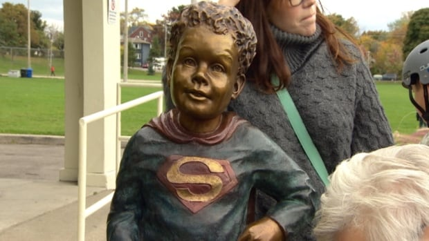 The life-sized bronze likeness of Jeffrey Baldwin poses heroically in Greenwood Park, dressed as his own favourite hero Superman.
