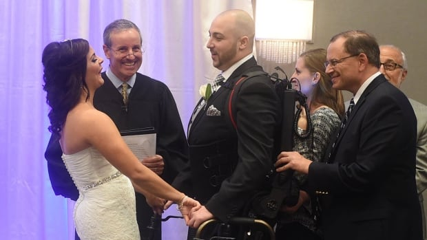 Jordan Basile, left, and Matt Ficarra, centre, exchange wedding vows in Syracuse, N.Y. on Saturday. Ficarra, who was paralyzed in an accident in 2011, used a robotic-like device called an Ekso to walk down the aisle with the help of Nicole Smith, second right, and Frank Hyland from Good Shepard in Allenton Pa.