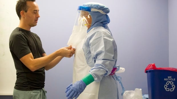 A health-care professional demonstrates protective equipment procedures at Toronto Western Hospital. The Canadian government said Monday it's strengthening public-health measures at borders and airports to prevent the spread of Ebola.