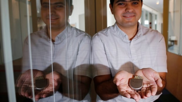 Massachusetts Institute of Technology researcher and graduate student Haitham Al-Hassanieh holds one of the Medtronic heart defibrillators he successfully attacked.