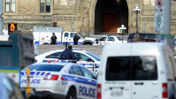 Police converge on Parliament Hill in Ottawa on Wednesday following shootings in the city. One soldier is dead after being shot at the National War Memorial.