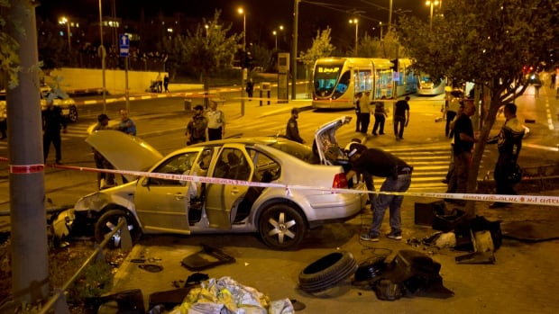 Israeli police officers inspect a car at the scene of the attack in Jerusalem.