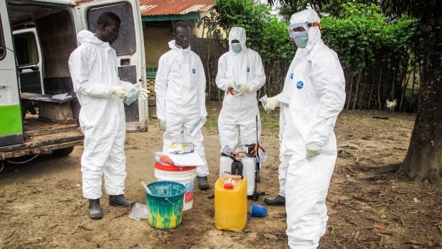 Health workers wear protective gear before entering the house of a person suspected to have died of  the Ebola virus on the outskirts of Freetown, Sierra Leone, Oct. 21. Canada has announced visa restrictions for residents for highly affected countries in West Africa.