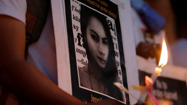 "A protester holds a lit candle in front of a portrait of slain Filipino transgender Jeffrey ""Jennifer"" Laude during a rally at the University of the Philippines campus at suburban Quezon city, northeast of Manila, on Oct. 24."
