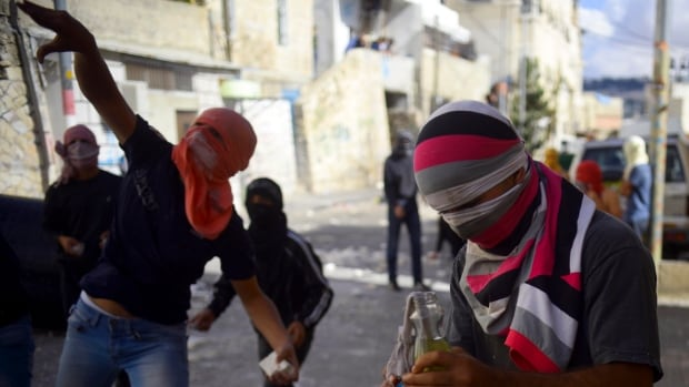 Palestinian youths throw stones during clashes with Israeli border police after Moatez Higazi, a man suspected of trying to kill a hard-line Jewish activist in Jerusalem, was shot in east Jerusalem on Oct. 30, 2014.
