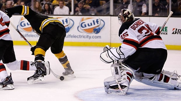 Boston Bruins centre Seth Griffith, left, scores a beautiful no-look, between the legs goal against Devils goalie Cory Schneider, right, Monday night.