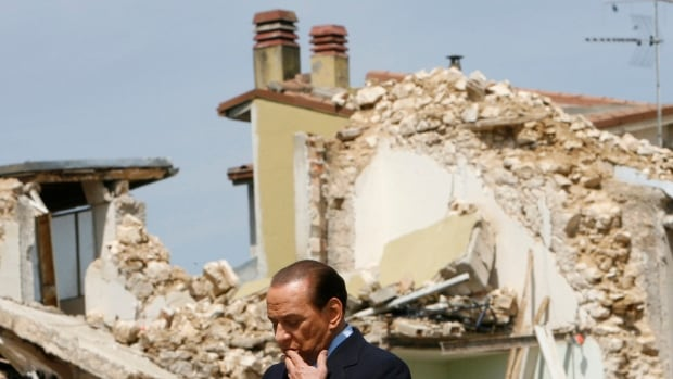 Italian prime minister Silvio Berlusconi pauses near buildings destroyed by an earthquake in the L'Aquila suburb of Onna April 25, 2009.  The earthquake killed more 300 people, leading to charges that experts failed to adequately warn local residents.