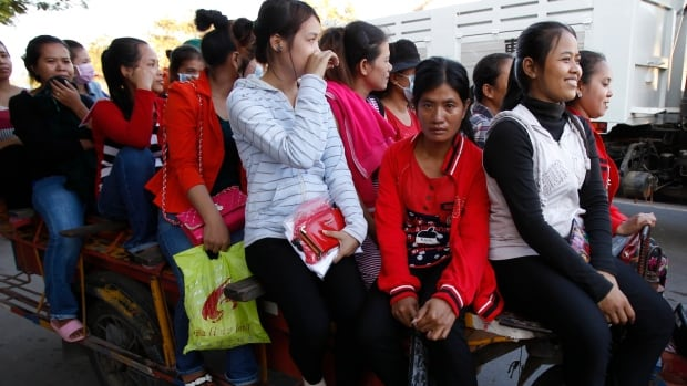 Cambodian garment workers sit on a motor cart heading home after their day's work in factory in Phnom Penh. Their wages have been increased to $128 a month.