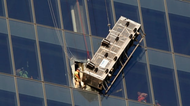 Workers look out at a broken scaffolding that had stranded window washers on the side of One World Trade Center in New York on Wednesday.
