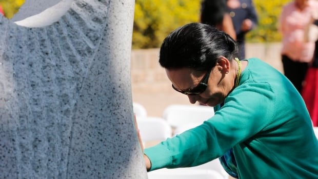 A woman reflects as she places her hand on a monument honouring Manitoba's missing and murdered women and girls which was unveiled in Winnipeg in August. Senators Serge Joyal and Lillian Dyck are are in the early stages of finding someone who will take the case to Federal Court.