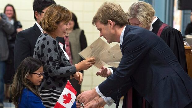 Chris Alexander, citizenship and immigration minister, hands out a Canadian flag at a citizenship ceremony in Dartmouth, N.S., last month. The federal government is appealing a court ruling that found a new appeals division for refugee claimants has been using too narrow a scope to conduct its work.