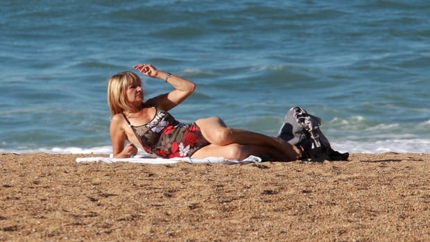 An unidentified woman sunbathes on the beach in Anglet southwestern France, where the temperature reached 22 degrees Celsius (71.6 degrees Fahrenheit), today. The National Oceanic and Atmospheric Administration said Thursday that so far this year, 2014 is the warmest year on record.