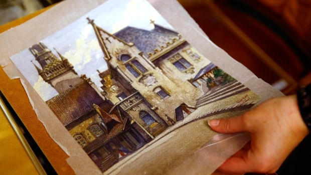 An employee puts away a watercolour of the old registry office in Munich by former German dictator Adolf Hitler at Weidler auction house in Nuremberg on Nov. 18.
