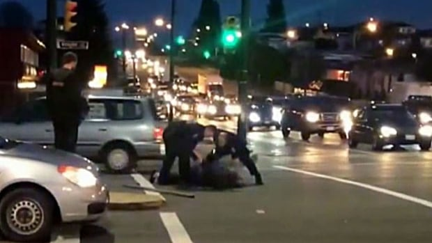 Vancouver police attend to a 51-year-old man seconds after he was shot Saturday afternoon. The two-by-four police say he was using to threaten them lies near the man's body.